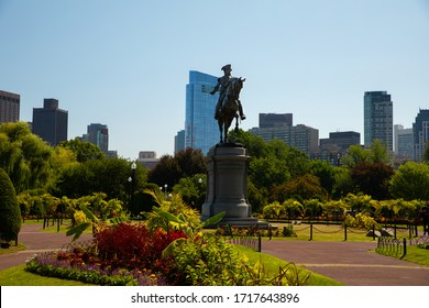 Boston Massachusetts, US-July 13th 2018: Tranquil 19th Century Urban Park with Boating lake and swan Boats and the Statue of George Washington.