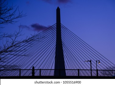 Boston, Mass./USA - March 25, 2018. A pedestrian walks over the Charlestown Bridge at dusk, with the Zakim Bridge looming in the background.