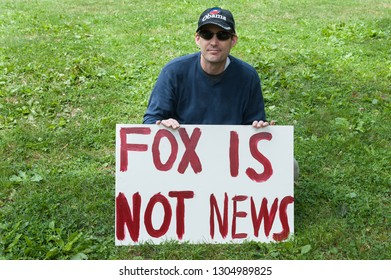 """Boston, MA/USA- September 7, 2009: A participant in a Labor Day protest in the Boston Common supporting national healthcare reform sits on the grass holding a sign reading """"FOX IS NOT NEWS."""""""