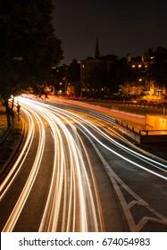 Boston at night. Cars passing under a footbridge on Storrow Drive.