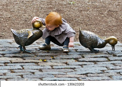 BOSTON - Oct.18, 2011: A little girl plays with the 'Make Way for Ducklings' bronze duck sculpture in the Boston Public Garden, site of the annual Mother's Day Duckling Parade.