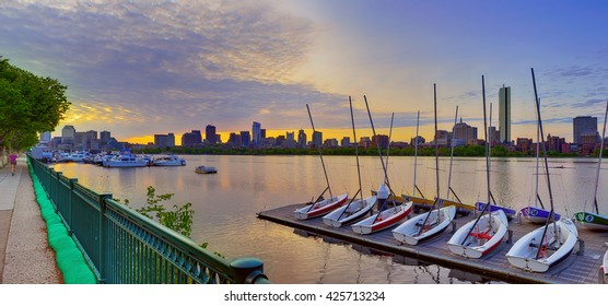 Boston skyline at dawn, boats docked in the Charles and early birds running and rowing