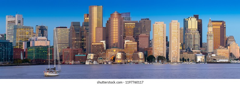 Boston skyline panorama at dawn with sailboat in foreground and blue sky