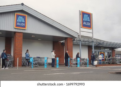 BOSTON UK, April 2. 2020: Queue of people practising the new social distancing rules outside Aldi supermarket