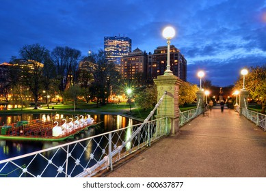 BOSTON, USA - APRIL 29: Locals and tourists walking by Lagoon Bridge and famous swan boats at Boston Public Gardens, Boston, Massachusetts, USA on a spring night of April 29, 2016.