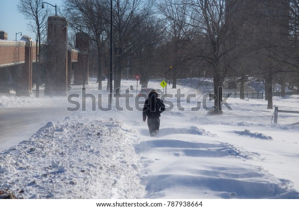 Boston, USA - January 5 2018: Person walking on a snow-covered sidewalk.