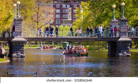 BOSTON, USA - JUNE 20: The architecture of the Boston Public Garden in Boston, Massachusetts, USA with its landscape and famous footbridge with lots of people enjoying the weather on June 20, 2017.