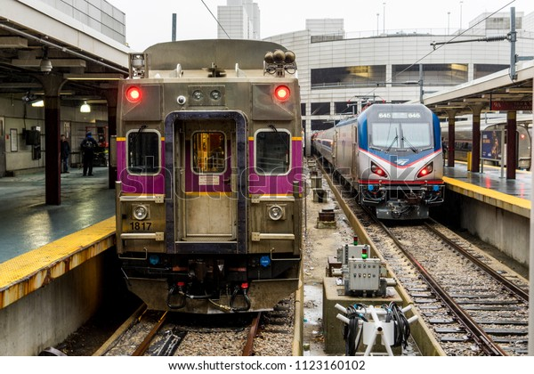 BOSTON, USA - MARCH 7, 2018: : Boston MBTA Purple Line Commuter Train and Amtrak train stopped at South Station, Massachusetts, USA
