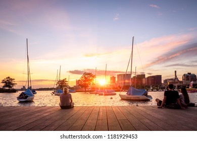 BOSTON, USA - SEPTEMBER 2, 2018: Local people in Boston enjoying a warm sunset by the Charles River overlooking Cambridge in Massachusetts, USA.