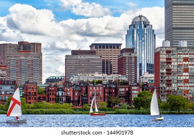 Boston's historic Back Bay neighborhood viewed from the Charles River, with recreational sailboats in the foreground. Blue sky with beautiful white clouds.