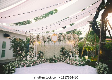Botanic chic at wedding. Ceremony decoration colors green and white, vintage doors, geometric objects, flowers and greenery.Retro style.