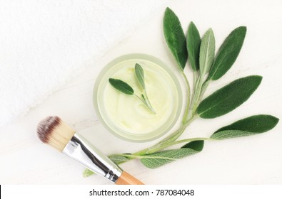 Botanical spa treatment with holistic sage plant. Body mask container with green leaves, top view preparation.