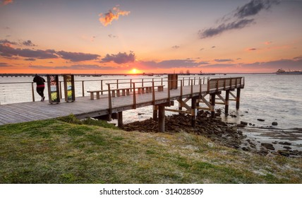 BOTANY BAY, AUSTRALIA - AUGUST 16, 2015; Golden sun setting over Botany Bay on a beautiful winter's day.  The place of Captain Cook's landing.  Cargo ships of Port Botany in the distance