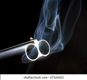 Both barrels on a double barreled shotgun that are smoking