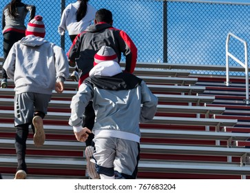 Both boys and girls track and field team running up bleachers on a cold sunny day.