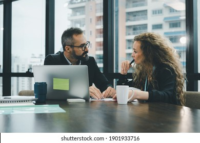 Both of executive officer are looking at each other while they are thinking or creating new project in the meeting. He is writing the idea detail in the document. - Shutterstock ID 1901933716