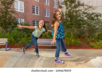 Both girls are on top of interactive outdoor sculpture. They are challenging each other to see who can stay on the longest by standing on one leg.