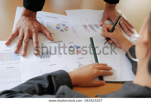 Both hands of sales manager place on business reports in front of a younger sales person.Very serious situation.