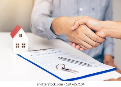 Both home sales agents and buyers work on signing new homes and shaking hands.