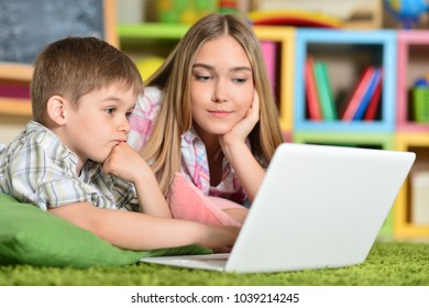 Bother and sister using laptop