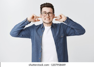 Bothered and irritated upset cute young man in glasses clenching teeth from dissatisfaction frowning closing ears with index fingers being annoyed with loud awful noise over white background
