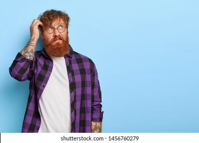 Bothered thoughtful bearded man with curly ginger hair, scratches head, thinks something over, tries to make decision, focused away, dressed in casual outfit, isolated on blue background. Let me think