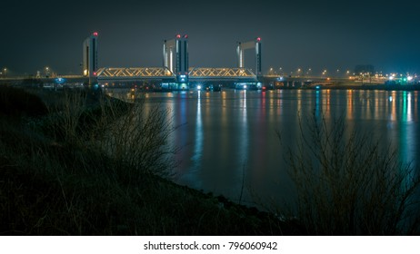 the botlekbrug over te river Maas near Pernis at night with the lights reflecting in the water