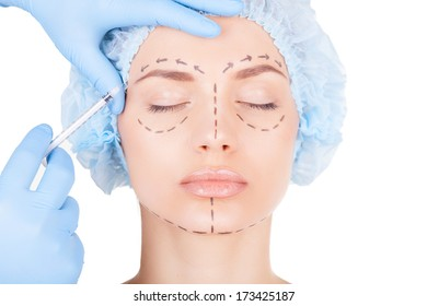 Botox injection. Attractive young woman in medical headwear and sketches on face keeping eyes closed while doctors hand making an injection in face