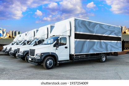 Botswana flag on the back of Five new white trucks against the backdrop of the river and the city. Truck, transport, freight transport. Freight and Logistics Concept