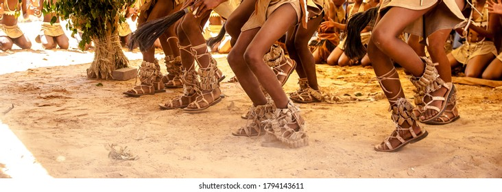 Botswana Traditional Dance Students Dancing To The Beat of Claps and Song In Khoisan Attire During A Ceremony Putting On Leg Rattles and Holding Traditional Whisk Made From Horse Tail Hair.