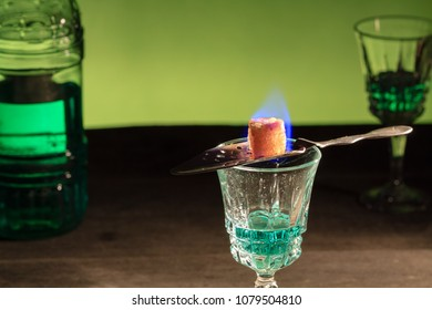 Bottle of absinthe and glasses with burning cube brown sugar.