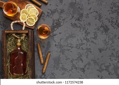 Bottle of aged brandy gift package shipping, two portions of drink, cigars and sliced lemon, black marble table, top view, copy space