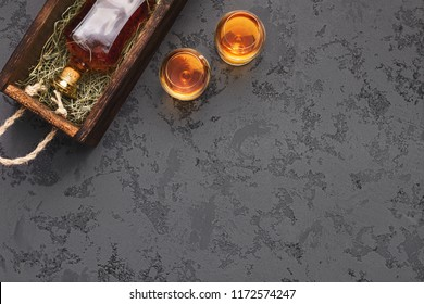Bottle of aged fine craft whiskey gift package shipping and two glasses on black marble table, top view, copy space