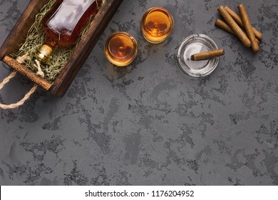 Bottle of aged whiskey gift package shipping with brandy and cigars on black marble table, top view, copy space