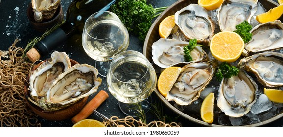 Bottle of aged wine and fresh oysters on a dark kitchen table. Seafood. Top view. Flat lay.