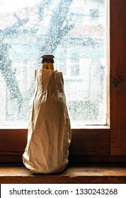 Bottle with alcohol in a brown pack paper placed to the window at rainy day. Wrinkled paper package. Hidden bottle alcohol in paper. Concept for stealthily drinking and alcoholism.