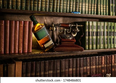Bottle with alcohol on a background of vintage books. Old retro telephone, authentic interior