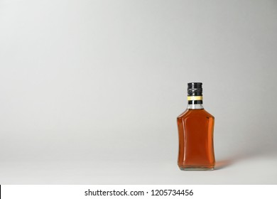 Bottle of alcoholic drink on grey background. Space for text