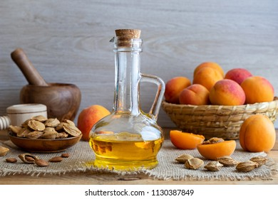 A bottle of apricot kernel oil with fresh ripe fruit