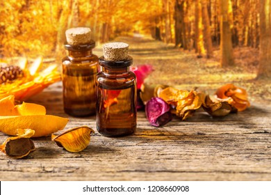 bottle of aroma essential oil with dry flower and mortar on wooden table over blurred autumn forest backgeound, spa concept.