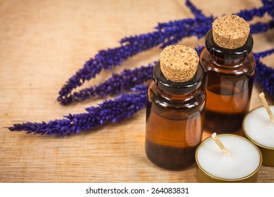 bottle of aroma essential oil with grass flower and candle on wooden background, spa concept.