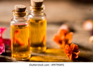 bottle of aroma essential oil or spa or natural fragrance oil with dry flower on wooden table, spa or alternative meditation aroma