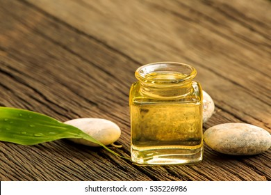 bottle of aroma essential oil or spa and natural green leave on wooden table, image for aroma spa alternative therapy medicine and meditation aroma concept.