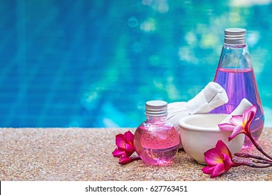 bottle of aroma essential oil or spa and natural fragrance oil with dry flower over blurred swimming pool, image for aroma spa alternative therapy medicine and meditation aroma concept.