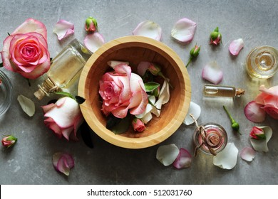 Bottle of aroma oil with roses in wooden bowl on table