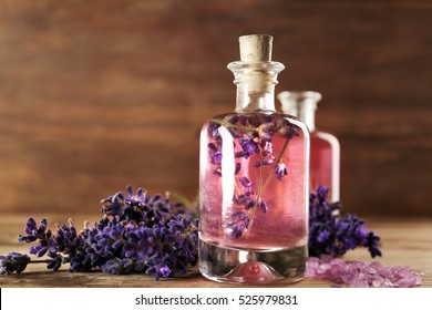 Bottle with aroma oil, sea salt and lavender flowers on wooden background
