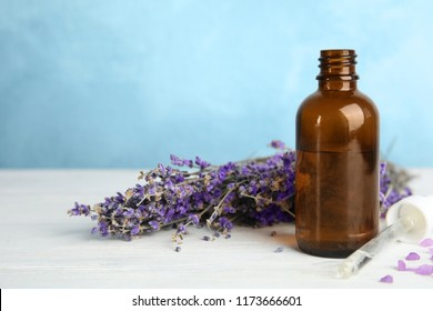 Bottle with aromatic lavender oil on wooden table. Space for text