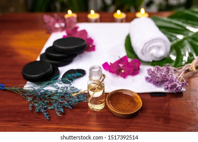 A bottle with aromatic oil, a cup with poured oil located in front of a terry towel on which are stones for therapy stone, a curled towel, pink flowers and dried lavender sprigs