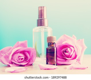 Bottle with aromatic oil and pink rose on wooden table