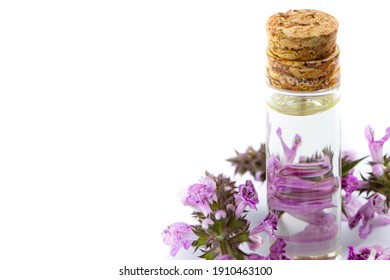 A bottle with aromatic oil surrounded by buds of lilac or pink flowers, close-up, copy space. - Shutterstock ID 1910463100